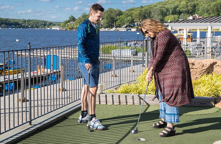 A woman about to make a putt while a man looks on