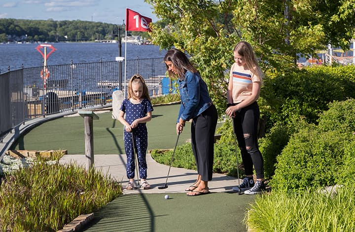 Three young women preparing to tee off at the start of a minigolf hole